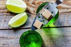 Absint i exponeringsglas med limefruktskivor på bästa sikt för träbakgrund Arkivfoton