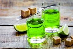 Absint i exponeringsglas med limefruktskivor på träbakgrund Arkivfoton