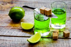 Absint i exponeringsglas med limefruktskivor på träbakgrund Royaltyfri Fotografi