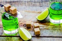 Absint i exponeringsglas med limefruktskivor på träbakgrund Royaltyfri Foto