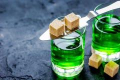 Absint i exponeringsglas med sockerkuber på mörk bakgrund Arkivbilder