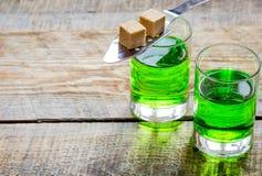 Absint i exponeringsglas med sockerkuber på träbakgrundsåtlöje upp Fotografering för Bildbyråer