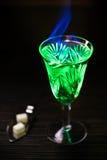 Absint i exponeringsglas och sked med kuber för vitt socker Royaltyfri Bild