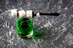 Absint i exponeringsglas på grått bakgrundsslut upp Arkivfoton