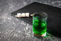 Absint i exponeringsglas på grått bakgrundsslut upp Royaltyfri Foto