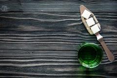 Absint i exponeringsglas på träåtlöje för bästa sikt för bakgrund upp Arkivbild
