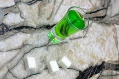 Absint med den sockerkuber och skeden på träbakgrund Fotografering för Bildbyråer