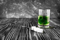 Absint med den sockerkuber och skeden på träbakgrund Royaltyfri Foto