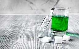 Absint med den sockerkuber och skeden på träbakgrund Arkivfoto