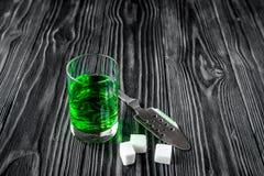 Absint med den sockerkuber och skeden på träbakgrund Royaltyfria Bilder