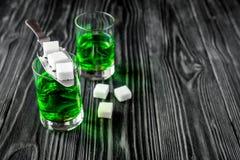 Absint med den sockerkuber och skeden på träbakgrund Arkivfoton