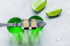 Absint med sockerkuber i sked på bästa sikt för stenbakgrund Arkivfoto