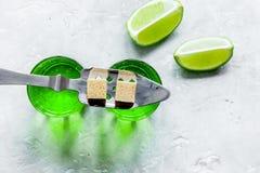 Absint med sockerkuber i sked på bästa sikt för stenbakgrund Arkivbild
