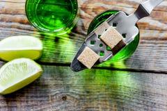 Absint med sockerkuber i sked på bästa sikt för träbakgrund Royaltyfri Fotografi
