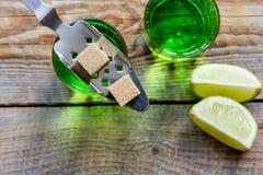 Absint med sockerkuber i sked på bästa sikt för träbakgrund Royaltyfria Bilder