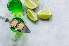 Absint med sockerkuber i sked på modell för bästa sikt för stenbakgrund Arkivfoto