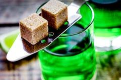 Absint med sockerkuber i sked på träbakgrund Royaltyfria Foton