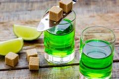 Absint med sockerkuber i sked på träbakgrund Royaltyfri Foto