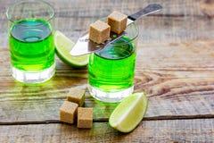 Absint med sockerkuber i sked på träbakgrund Royaltyfria Bilder