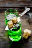 Absint med sockerkuber i sked på träbakgrund Arkivfoton