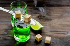 Absint med sockerkuber i sked på träbakgrund Royaltyfri Fotografi