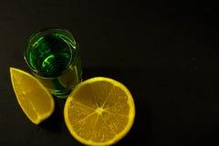 Absint och citron på svart bakgrund royaltyfri bild