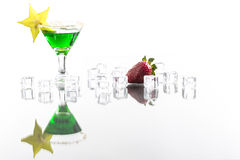 Absinth in cocktail glass decorated with ice cube and carambola Royalty Free Stock Images