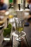 Absinth glass and fountain. Classic ritual of glass of absinth and dripping fountain Stock Images