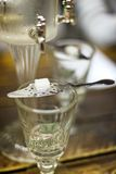 Absinth glass and fountain. Classic ritual of glass of absinth and dripping fountain Royalty Free Stock Photos