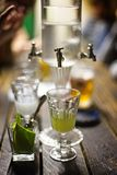 Absinth glass and fountain. Classic ritual of glass of absinth and dripping fountain Royalty Free Stock Photography