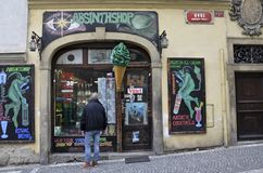 Absinth shop in Prague, Czech Republic. Man stares in window of a shop that sells Absinth, also known as Green Fairy; the green demons and green scoop of ice Stock Photo