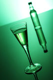 Absinthe. The original green absinthe spirit on a reflective surface stock image