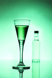 Absinthe. The original green absinthe spirit on a reflective surface royalty free stock photography