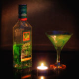 Absinthe. The photo shows the bottle of absinthe and a glass with a drink on the table stock image