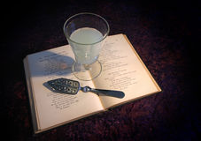 Absinthe on Book. A glass of absinthe on a 100 year old Edgar Allan Poe book. (Note Edgar Allan Poe is public domain Royalty Free Stock Photo
