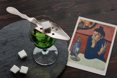 Absinthe in a glass. Alcohoil Absinthe, sugar cubes and classic french absinthe spoon, with a postcard `Absinthe lover` by Picasso Royalty Free Stock Photography