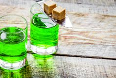 Absinthe in glass with sugar cubes on wooden background mock up. Green absinthe in glass with sugar cubes on wooden table background mock up royalty free stock photo