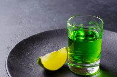 Free Absinthe Green Liquor In Glasses. Alcoholic Hallucinogenic Beverage. Dark Background. Pieces Of Limein A Plate. Copy Space Royalty Free Stock Images - 156409449
