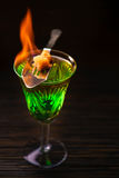 Absinthe prepared for drinking. Blazing absinthe with sugar pieces on special spoon. Vertical studio shot royalty free stock photos