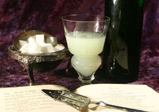 Absinthe scene. Glass of absinthe with sugar and an open Edgar Allan Poe book Stock Photos