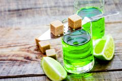 Absinthe shots with lime slices and sugar on wooden table backgr Royalty Free Stock Photography