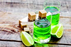 Absinthe shots with lime slices and sugar on wooden table backgr Stock Photos