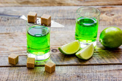 Absinthe shots with lime slices and sugar on wooden table background Royalty Free Stock Photography