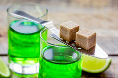 Absinthe shots with lime slices and sugar on wooden table background Stock Photos