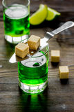 Absinthe shots with lime slices and sugar on wooden table background Stock Photo