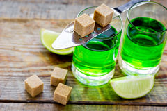 Absinthe shots with lime slices and sugar on wooden table background Stock Image