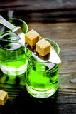 Absinthe shots with sugar on wooden table background Stock Photography