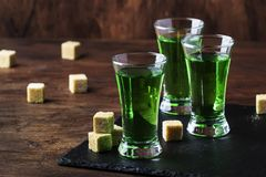 Absinthe - strong alcoholic drink, green bitter wormwood tincture in glasses on the old wooden table, place for text. Absinthe - strong alcoholic drink, green royalty free stock photo