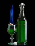 Absinthe with sugar burning. Absinthe bottle and glass with lump sugar burning royalty free stock photography
