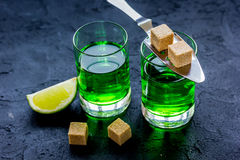 Absinthe with sugar cubes in spoon on dark background. Green absinthe with sugar cubes in spoon on dark table background Royalty Free Stock Photo
